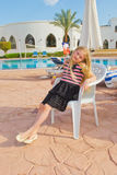 Girl by the pool. Girl sitting on a chair relaxing at the pool with blue water Stock Photography