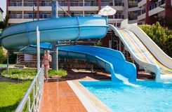 Girl at the pool with slides at resort stock images