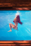 Girl in pool underwater through the glass stock photo