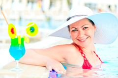 Girl in the pool in a white hat Stock Photography