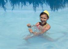 Girl in pool. Young girl swims play in pool Stock Image