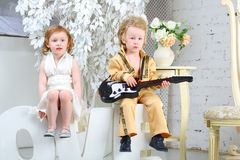 Girl and pop musician with guitar sit on letters Stock Images