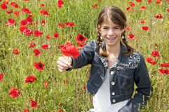 Girl with poppies giving flower Royalty Free Stock Photos