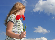 Girl with poppies over sky. Happy child with red poppies over sky royalty free stock photo