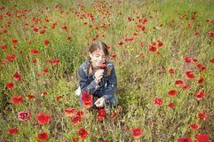 Girl with poppies squatting & smelling wide Royalty Free Stock Photography