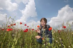 Girl with poppies squatting wide Royalty Free Stock Image