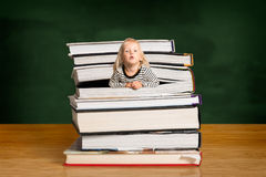Girl popping out of the pile of books stock photo