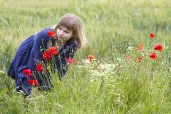 Girl in poppy field Stock Photography