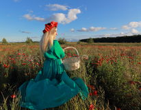Girl on a poppy field. Relax of the girl in the field with poppies Stock Photo
