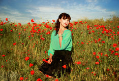 Girl in poppy field. Young wooman in poppy meadow royalty free stock image