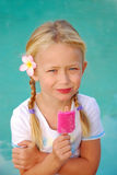 Girl with Popsicle. Pretty young blond girl holding a pink frozen Popsicle Royalty Free Stock Images