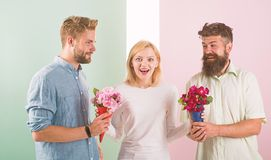 Girl popular receive lot men attention. Woman smiling can not choose partner, grabs both bouquets. Girl happy likes royalty free stock photography