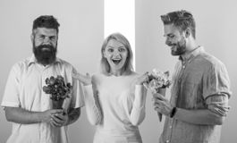 Girl popular receive lot men attention. Woman smiling has opportunity choose partner. Men competitors with bouquets royalty free stock images