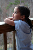 Girl on Porch. A girl looks into nature Stock Photography