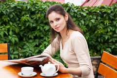 The girl on the porch reading a newspaper Royalty Free Stock Photos