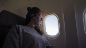 Girl at porthole in the plane. Young woman seating on passenger seat and looking out window on airplane. stock video