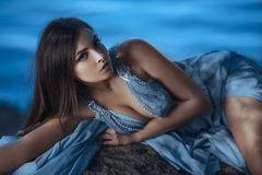 Girl Portrait. Art Fashion Photography. Fashion Art Photo. Model Girl Portrait in Moonlight at Night. Sexy Glamour Mystical Beautiful Woman in blue dress laying Royalty Free Stock Images