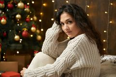 Girl portrait in christmas lights and decoration, dressed in white sweater and stockings, fir tree on dark wooden background, wint. Er holiday concept Royalty Free Stock Photos