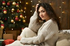 Girl portrait in christmas lights and decoration, dressed in white sweater and stockings, fir tree on dark wooden background, wint. Er holiday concept Royalty Free Stock Image
