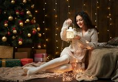 Girl portrait in christmas lights and decoration, dressed in white sweater and stockings, fir tree on dark wooden background, wint. Er holiday concept Stock Photos