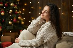 Girl portrait in christmas lights and decoration, dressed in white sweater and stockings, fir tree on dark wooden background, wint. Er holiday concept Royalty Free Stock Photo