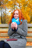 Girl portrait with cup and book on yellow leaves background, autumn season Stock Images