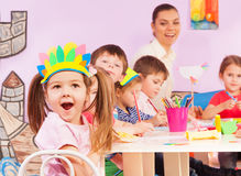Girl portrait and kindergarten class. Nice little girl close-up portrait and group of kids boys and girls with teacher in early developing kindergarten class royalty free stock photography