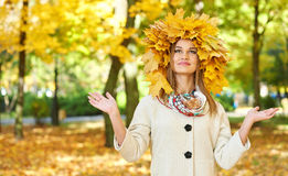 Girl portrait with leaves on head in autumn city park Royalty Free Stock Image