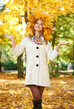 Girl portrait with leaves on head in autumn city park Stock Image
