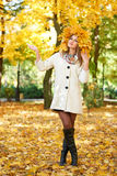 Girl portrait with leaves on head in autumn city park Stock Photography