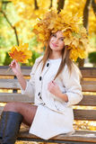 Girl portrait with leaves on head in autumn city park Stock Photo