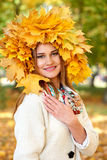 Girl portrait with leaves on head in autumn city park Royalty Free Stock Photo