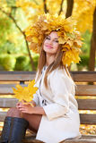Girl portrait with leaves on head in autumn city park Royalty Free Stock Photos