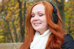 Girl portrait, listen music on audio player with headphones, sit on bench in city park, autumn season, yellow trees and fallen lea Royalty Free Stock Photos
