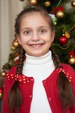 Girl portrait near christmas tree, happy holiday and winter celebration, dressed in red Stock Photos