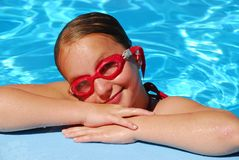 Girl portrait pool. Portrait of a young girl in red goggles resting at the pool edge Royalty Free Stock Photo