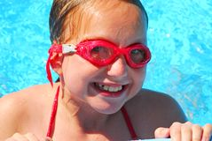 Girl portrait pool. Portrait of a smiling girl in red goggles resting at the pool edge Royalty Free Stock Photography