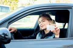 Girl portrait sititng in her car and driving license. Young girl holding her new driving license seated in the car royalty free stock photo