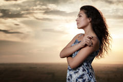 Girl portrait at sunset on evening sky background Royalty Free Stock Image