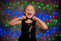 Girl portrait. Girl wearing black dress and bow tie with Christmas lights Stock Images