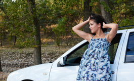 Girl portrait with white auto posing on road Royalty Free Stock Photos