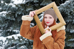 Girl portrait in wooden photo frame at winter season. Snowy weather in fir tree park. Royalty Free Stock Images