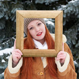 Girl portrait in wooden photo frame at winter season. Snowy weather in fir tree park. Stock Image