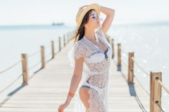 Girl pose at sea pier in straw hat and sunglasses. Woman in sexy swimsuit on tropical beach on sunny blue sky. Summer vacation. Re Royalty Free Stock Images