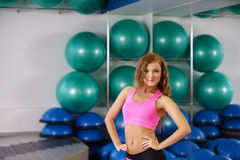 Girl poses on backdrop of stand with fitness balls Stock Photos