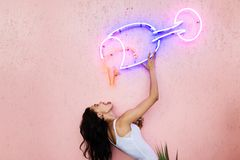The girl poses on the pink wall, pretending to drink from a glass made of neon tubes attached to the wall stock photo
