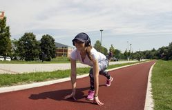 The girl poses and stretches her legs on the running track. She is about to start running stock photos