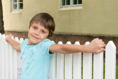 The girl poses on a white fence Stock Photo