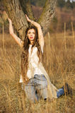 Girl posing against tree. In high grass Stock Photo