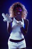 Girl posing with artificial snow under UV light Stock Photos